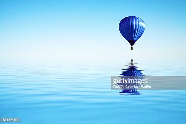 Blue Hot Air Balloon Flying Over Sea Against Sky