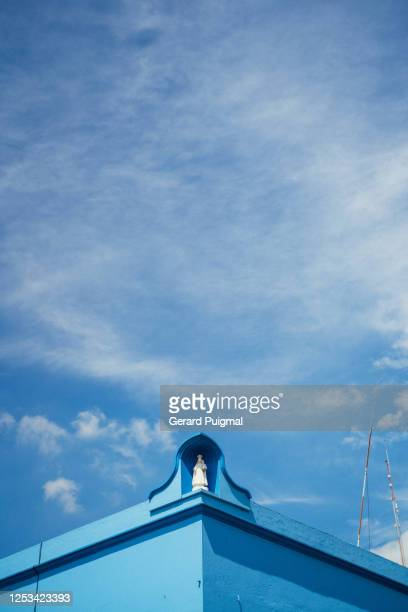 """blue house in oaxaca (oaxaca state, mexico) and virgin mary on blue sky - """"gerard puigmal"""" stock pictures, royalty-free photos & images"""
