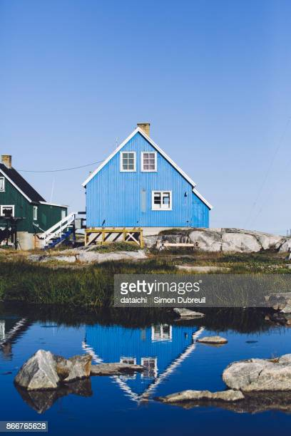 Blue house reflection in Qeqertarsuaq village on Disko Island
