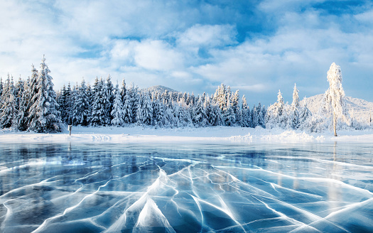 Blue ice and cracks on the surface of the ice. Frozen lake under a blue sky in the winter. The hills of pines. Winter. Carpathian, Ukraine, Europe. 853844276