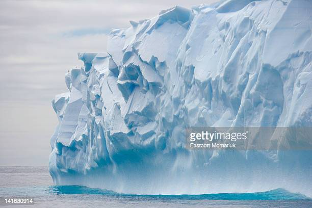 blue iceberg carved by waves floats in calm sea - iceberg photos et images de collection