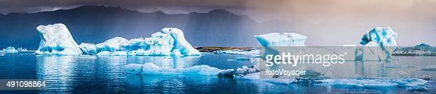 Blue icebergs floating along storm Arctic coast panorama Jokulsarlon Iceland