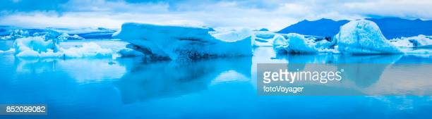 Blue icebergs reflecting in tranquil Arctic Ocean lagoon panorama Iceland