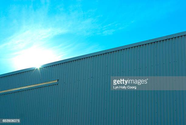 blue industrial building with sunlight - lyn holly coorg stock pictures, royalty-free photos & images