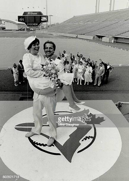 Blue Jay bells Manfred Schuhmann holds his new wife Arlene Parsons at Exhibition Stadium yesterday after the two were married at home plate About a...