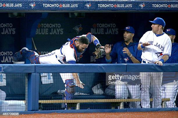 TORONTO ON AUGUST 11 Blue Jays catcher Russell Martin falls into the dugout while trying to catch a foul ball while pitcher David Price and Cliff...