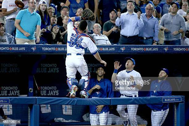 TORONTO ON AUGUST 11 Blue Jays catcher Russell Martin trying to catch a foul ball while David Price Cliff Pennington and Mark Buehrle look on in the...