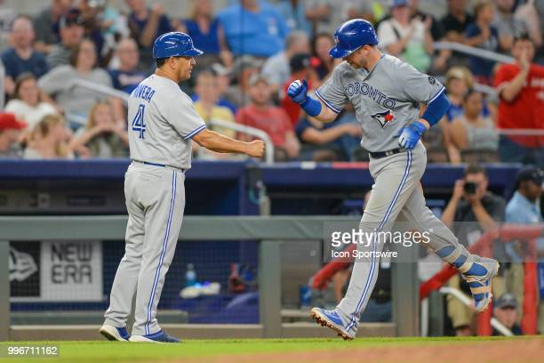 Blue Jays infielder Justin Smoak is congratulated by third base coach Luis Rivera after hitting a solo home run during the game between Atlanta and...