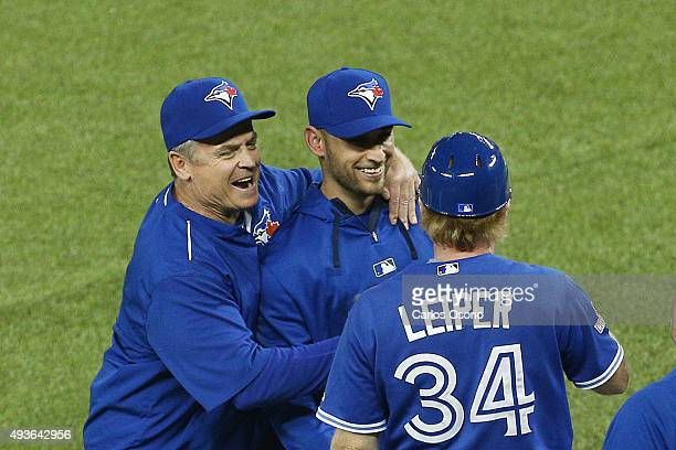 Blue Jays manager John Gibbons hugs pitcher Marco Estrada while 1B coach Tim Leiper looks on after game 5 of the American League Championship Series...