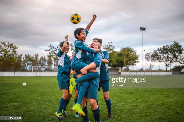 blue jersey boy footballers cheering and celebrating - soccer competition stock pictures, royalty-free photos & images