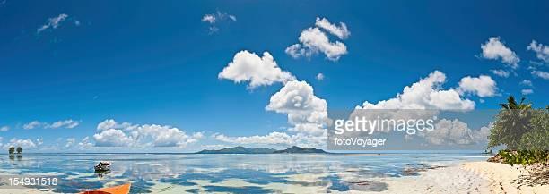 Blue lagoon beach reflecting panoramic tropical island sky fluffy clouds