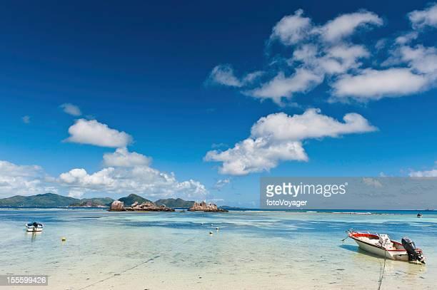 ブルーのラグーンに停泊するボートのどかな島のビーチ