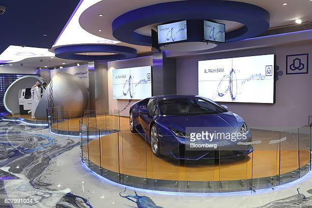 A blue Lamborghini automobile manufactured by Automobili Lamborghini SpA sits on display inside the Al Rajhi Bank as customers use automated teller...