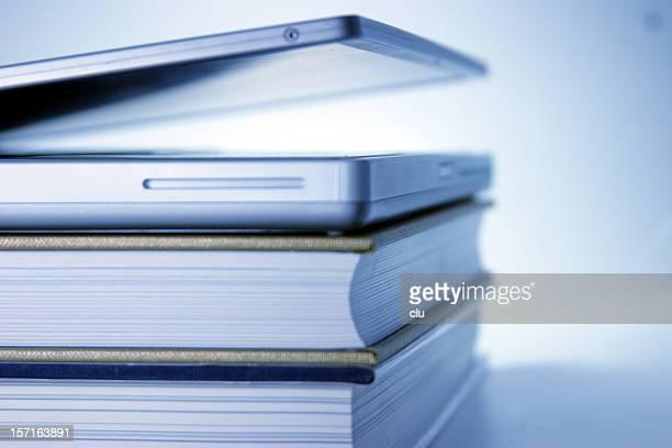 Blue Laptop slightly opened lying on  books