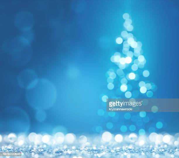 blue light and christmas tree on white defocused sparkles - christmas wallpaper stock pictures, royalty-free photos & images