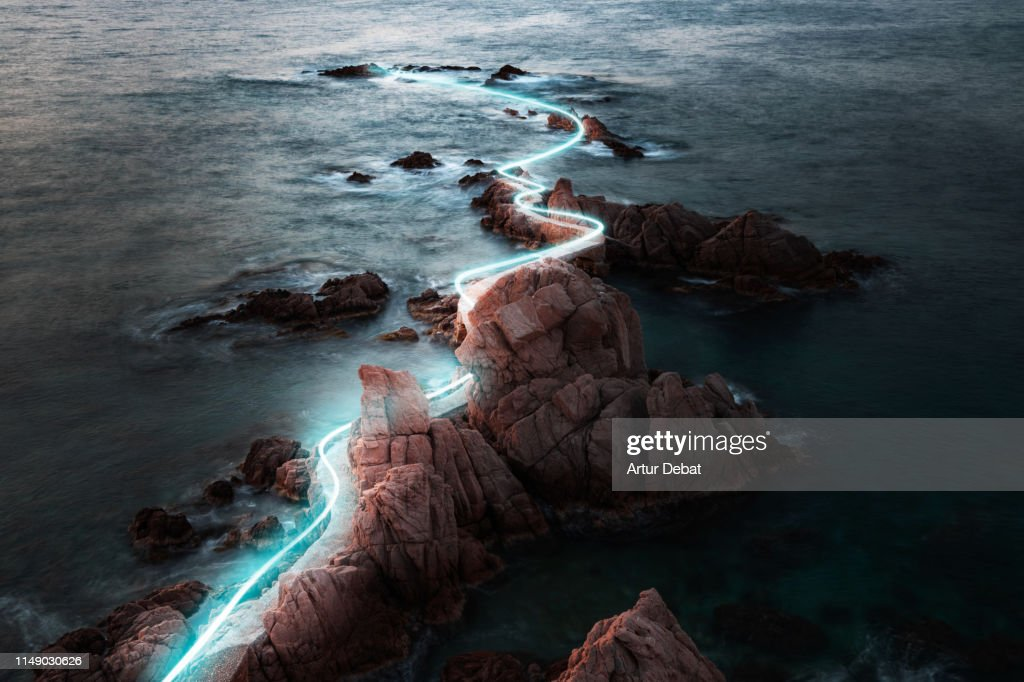 Blue light trail following footpath between the stunning coastline during sunrise. : Stock-Foto