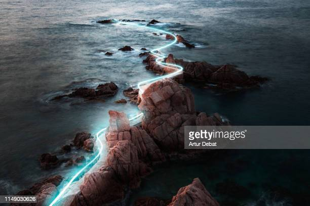 blue light trail following footpath between the stunning coastline during sunrise. - futuristisch stockfoto's en -beelden