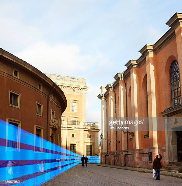blue light trail travelling between old buildings. - between stock pictures, royalty-free photos & images