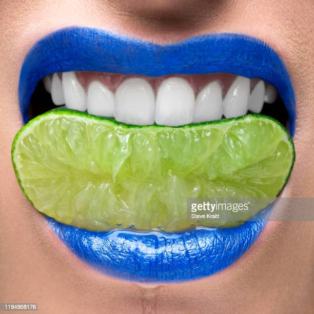 blue lips biting on lime slice - food and drink stock pictures, royalty-free photos & images