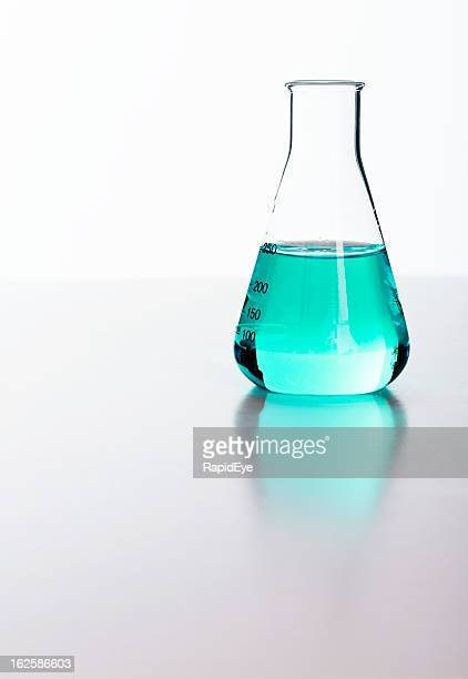 Blue liquid in lab flask reflected on perspex against white