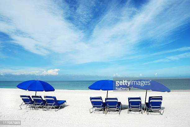 blue lounge chairs and sun umbrellas on a white sand beach - marco island stock pictures, royalty-free photos & images