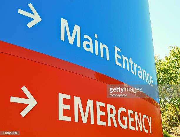 Blue main entrance and red emergency hospital signs
