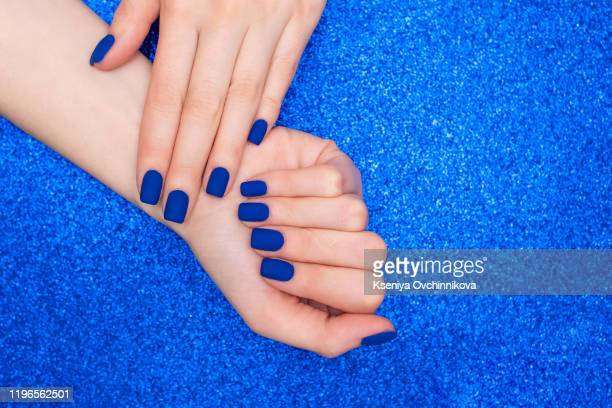 blue manicure in light and dark colors of lacquer on a striped background. - oval kennington stock pictures, royalty-free photos & images