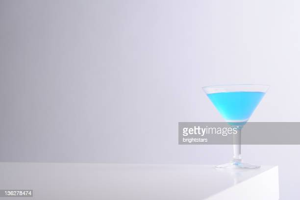 Blue martini glass on white table