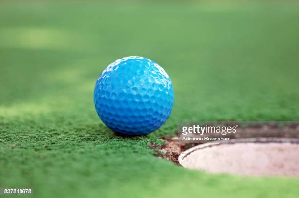 blue mini golf ball on grass near hole - miniature golf stock photos and pictures