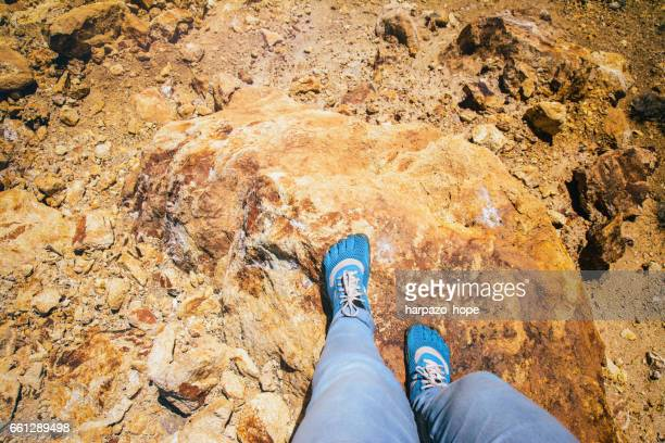 Blue minimalist shoes on rust colored rock.