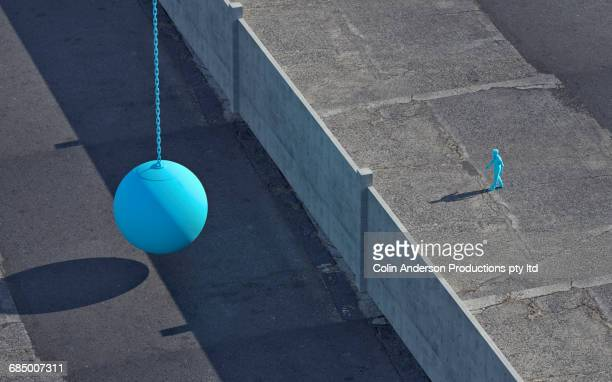 Blue Mixed Race man walking to wall near wrecking ball