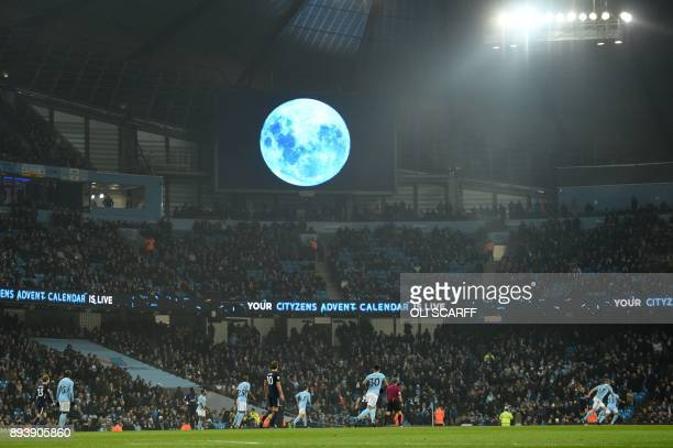 A blue moon is projected onto a big screen during the English Premier League football match between Manchester City and Tottenham Hotspur at the...