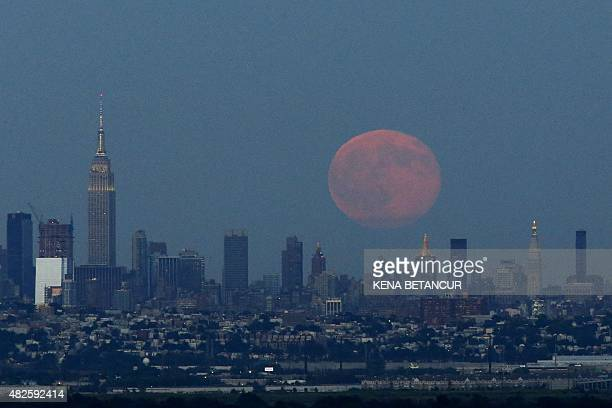 A Blue Moon rises over the skyline of New York City from West Orange in New Jersey on July 31 2015 PHOTO/KENA BETANCUR