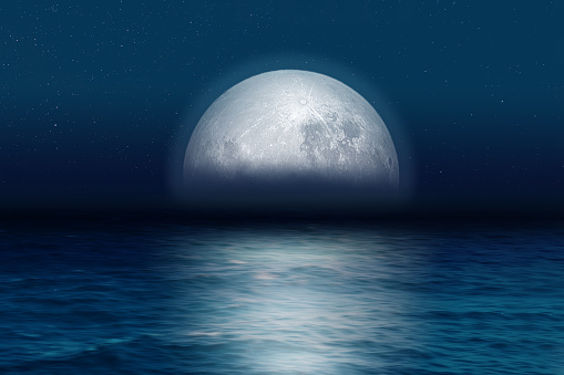 Blue moon rising at night over the sea. - gettyimageskorea