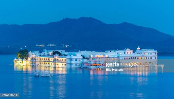 Blue morning dawn sunlight reflects off the Lake Palace on the island of Jag Niwas in Lake Pichola, Udaipur, India.