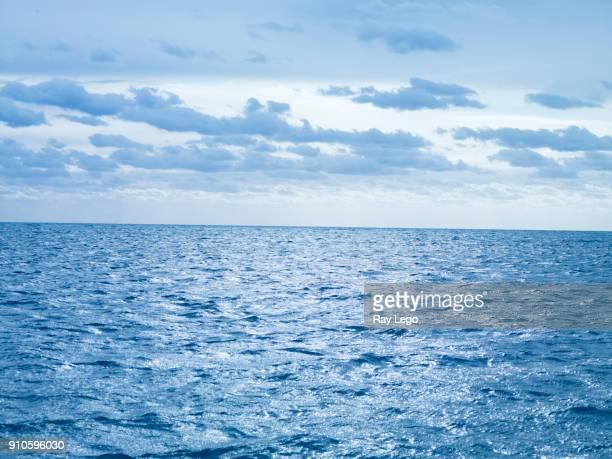 blue morning light over the ocean with clouds, off the cost of usa. - horizon over water stock pictures, royalty-free photos & images