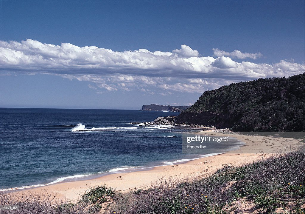 blue ocean water splashes on a sandy beach covered with dead plants and green grasses as rock formations rise in the distance under a blue sky and white clouds : Foto de stock