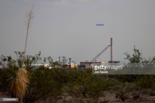 Blue Origin's New Shepard crew capsule descends on the end of its parachute system carrying Jeff Bezos along with his brother Mark Bezos, 18-year-old...