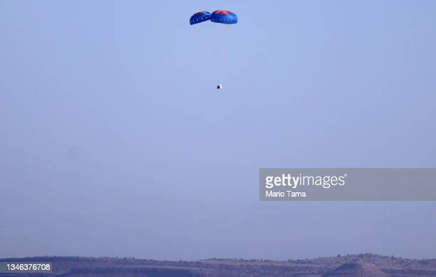 Blue Origin's New Shepard crew capsule descends on the end of its parachute system carrying 90-year-old Star Trek actor William Shatner and three...