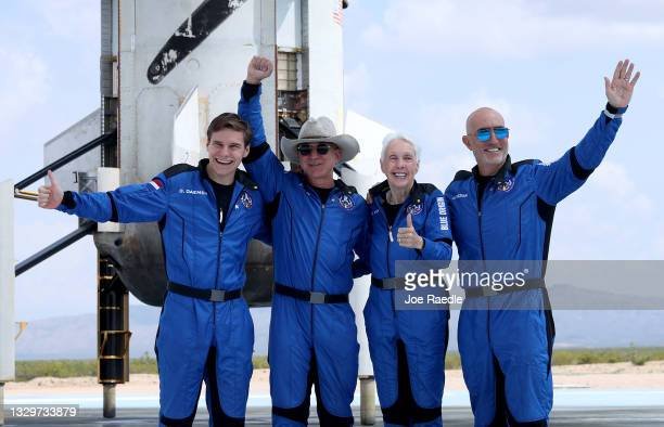Blue Origin's New Shepard crew Oliver Daemen, Jeff Bezos, Wally Funk, and Mark Bezos pose for a picture near the booster after flying into space in...