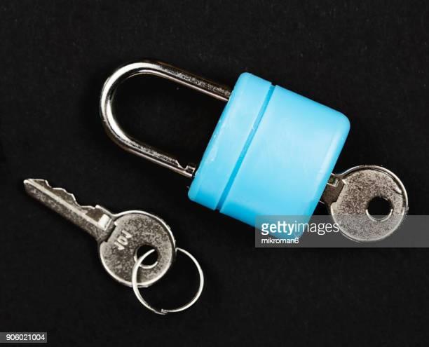 Blue padlock with key on black background