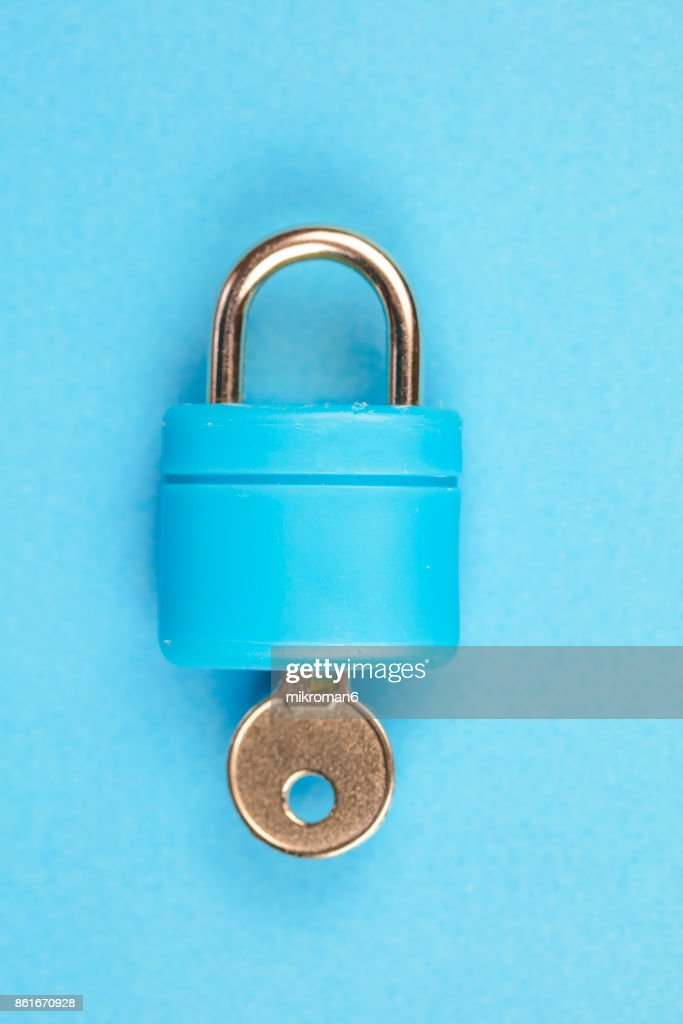 Blue padlock with key on blue background : Stock Photo