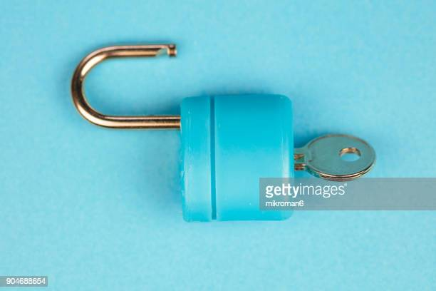 Blue padlock with key on blue background