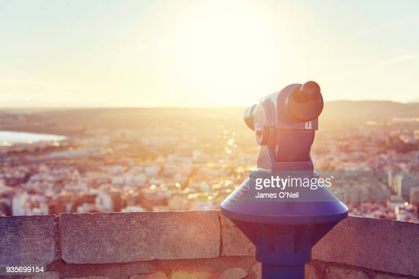 Blue paid telescope looking over city of Alicante at sunset, Spain