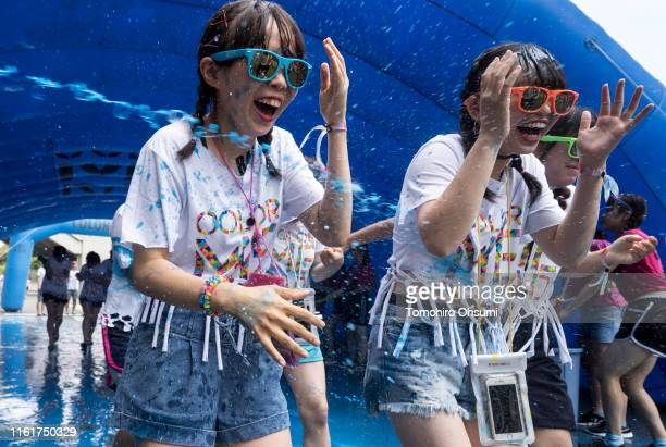 Blue paint is sprayed to participants during the Color Me Rad Tokyo 2019 at the Ajinomoto Stadium on July 13 2019 in Tokyo Japan Participants in the...