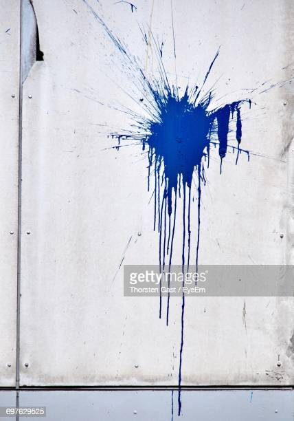 blue paint splashed on wall - spritzendes wasser stock-fotos und bilder