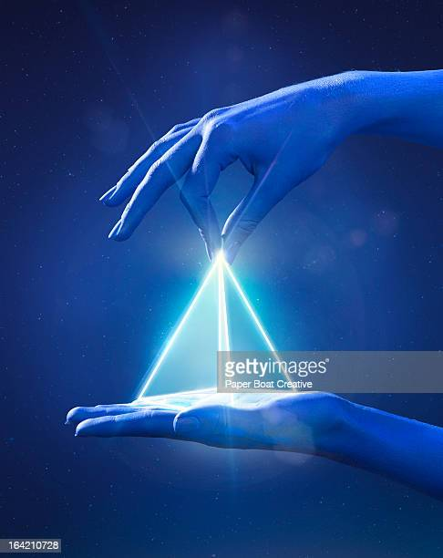 Blue painted hand pinching a glowing light prism