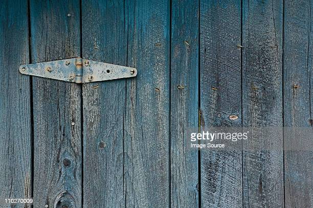 Blue painted wooden door with hinge