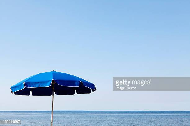 Blue parasol against the sea