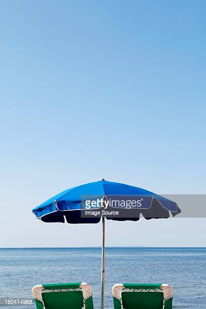 Blue parasol and sun loungers by the sea